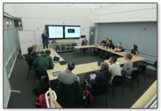 A picture of the Futurity classroom, taken by one of the authors (Hartman). Eleven students are seated around tables arrayed in a horseshoe fashion. They face a double screen at the front of the room. One screen has a PowerPoint projected onto it and one screen has Lacuna projected on to it. The instructors flank the screens, one sitting and one standing. Four students have laptops open, but all appear to be engaged in the conversation.