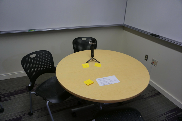 Figure 1: An image of a small room with two empty chairs and a table. On the table is a video camera on a tripod, and a list of questions that contain the prompts for the video.
