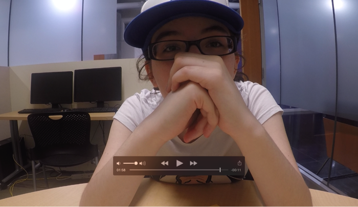 Figure 2: An image of a student sitting in front of a camera with hands clasped together in front of her face.