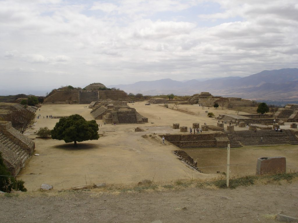 Fig. 1 – Large open plaza of archaeological site of Monte Albán, pyramid mounds close by and mountains visible in the distance.