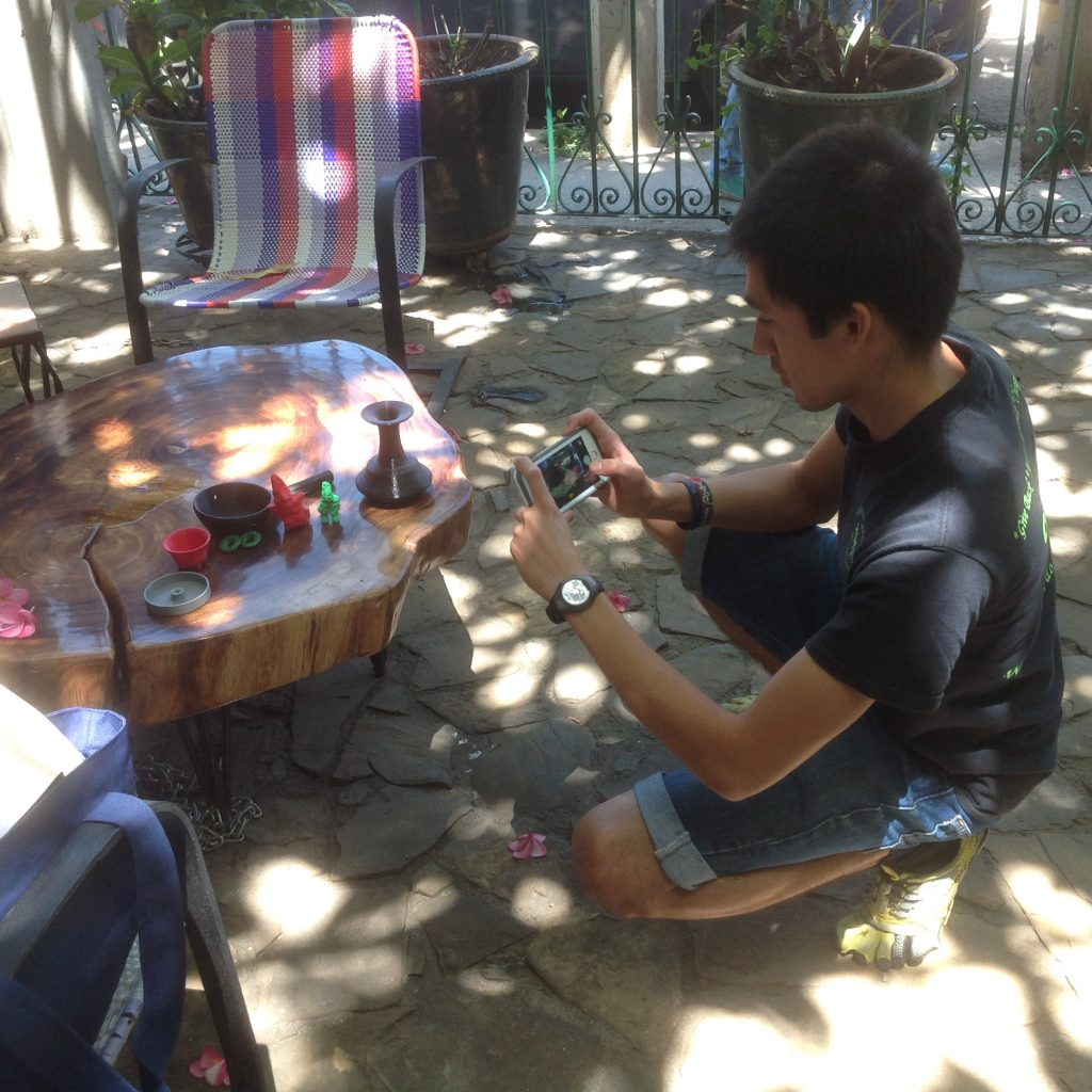 Fig. 11 – Young man with a camera kneels by a table with several plastic objects on it, taking a photograph of them.