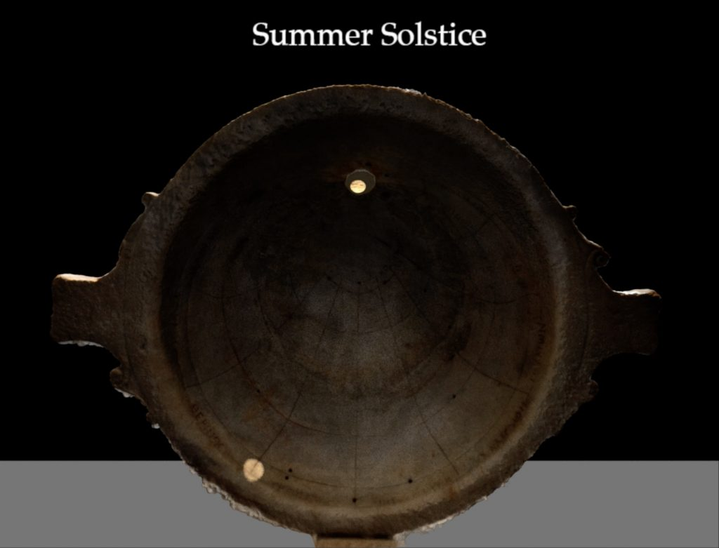 Roofed Spherical Sundial showing the hour before midday on the summer solstice. Much of the interior surface of the sundial is in shadow and there is a bright spot of light indicating the hour of the day.