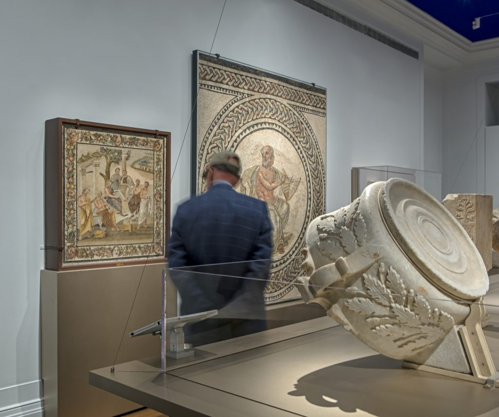 "Installation view showing carved exterior of the Roofed Spherical Sundial with Greek Inscription (right) and Roman Mosaic Depicting the Seven Sages (""Plato's Academy"") on opposite wall (left), 2016. There is a single visitor shown in the image."