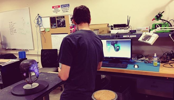 Student using Artec 3D scanner in engineering lab to scan football helmet from Georgia Tech Archives