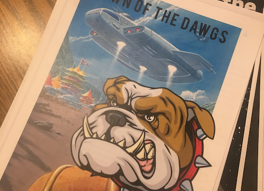 Printed pages, bound with a ring; top page includes a landing spaceship and a bulldog mascot.
