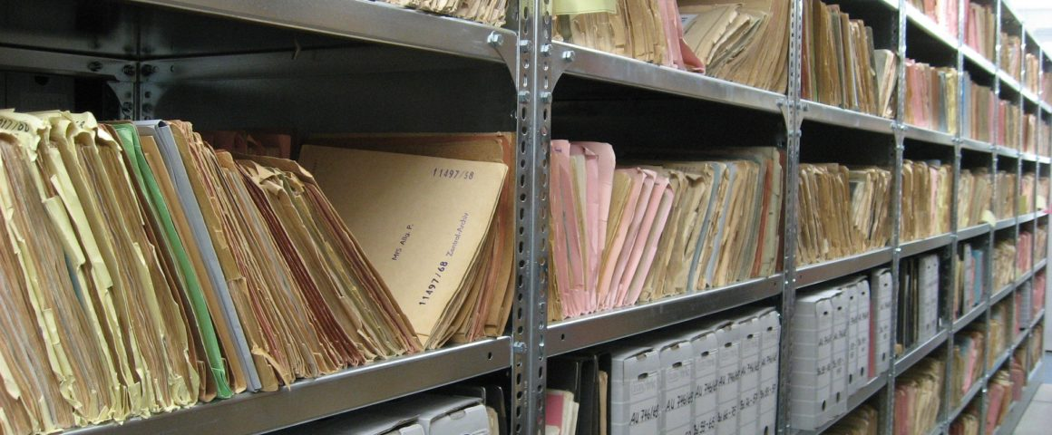 A photo of shelves of paper files in an archive.