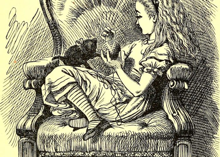 Alice in Wonderland sitting in a chair playing with her kitten and a ball of yarn.
