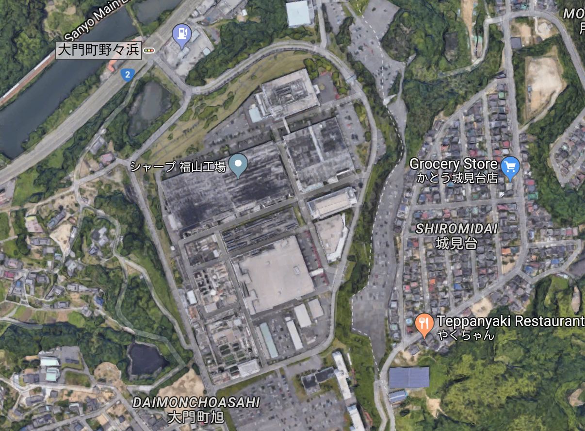 A screenshot of an aerial or satellite view of a factory in Japan. Nearby there is a river and a residential area.