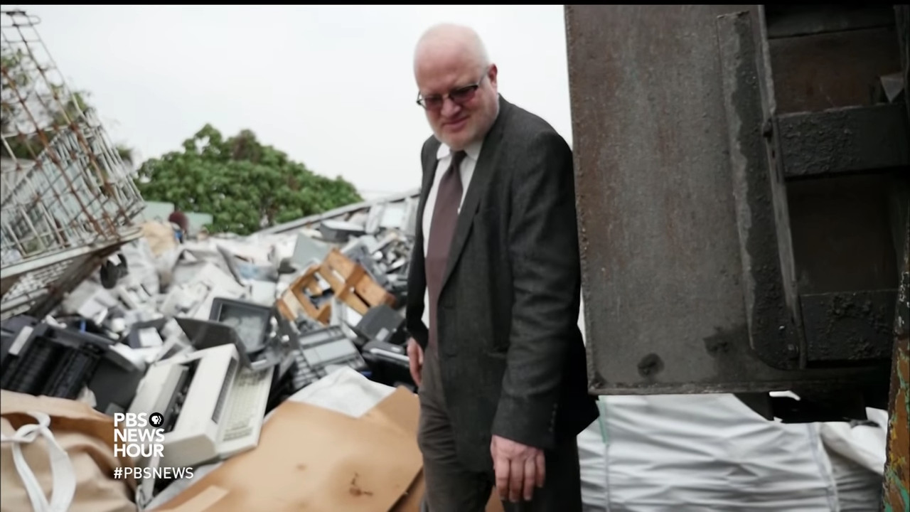 A man (Jim Puckett) looks at a pile of electronic waste.