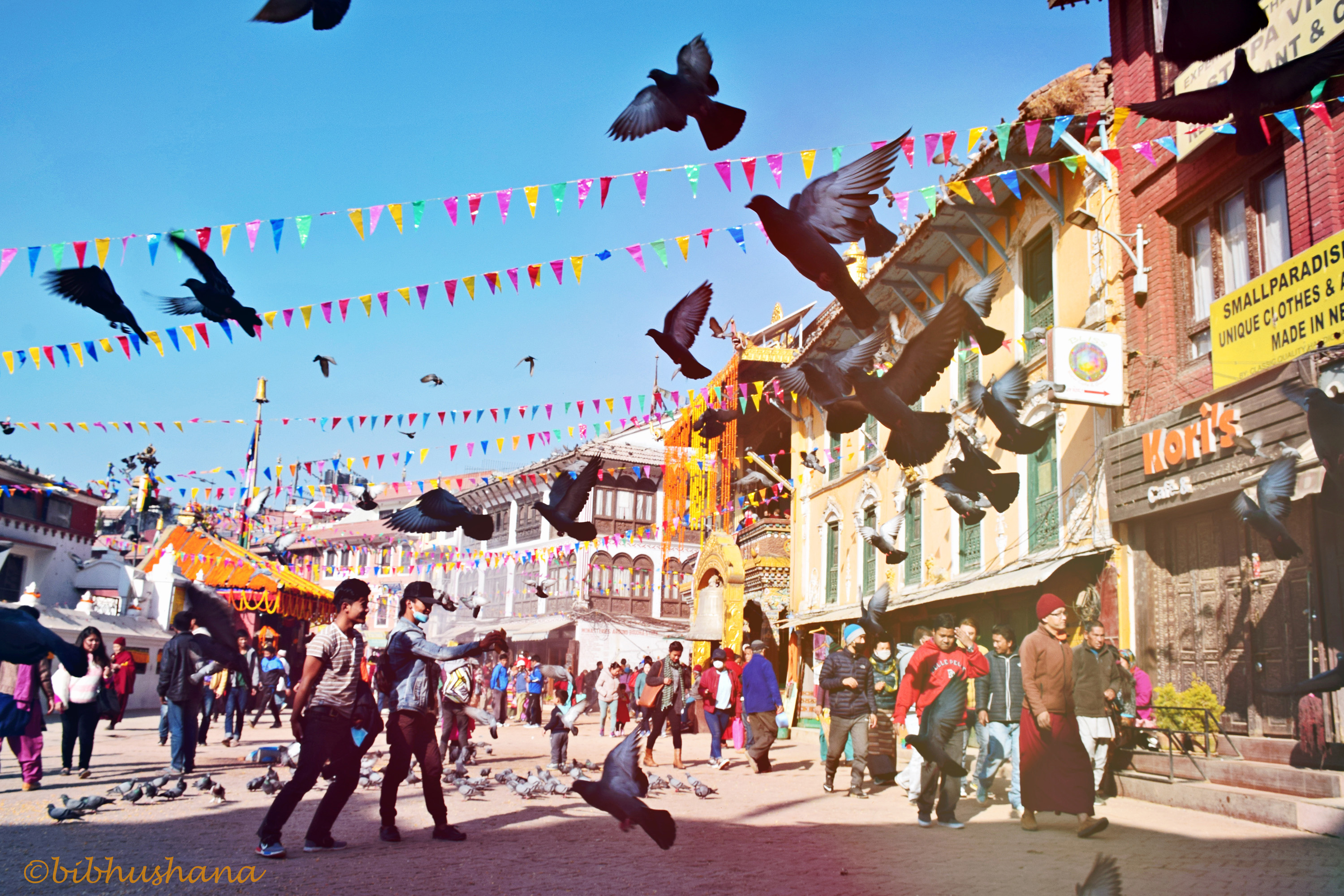Image depicts the streets of Kathmandu, Nepal. People walk in various directions as birds fly overhead. Pigeons, strollers, and passersby surround Boudhanath Stupa in the morning.