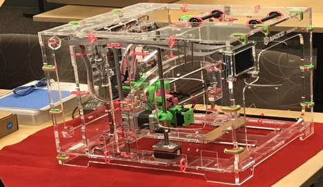 Clear plastic Jellybox 3D printer completely built with pink zip ties and lime green motors.