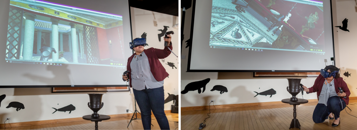 Graduate student wearing a virtual reality headset in front of a projector displaying a room, and standing next to a table displaying a black 3D printed version of the calyx krater.