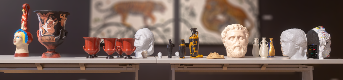 Landscape view of a table display presenting multiple 3D printed versions of antiquities within the Lowe Art Museum.