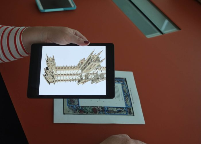 A hand holds a digital tablet over a page of text with a decorative border, while the tablet's screen displays a 3D model of a cathedral.