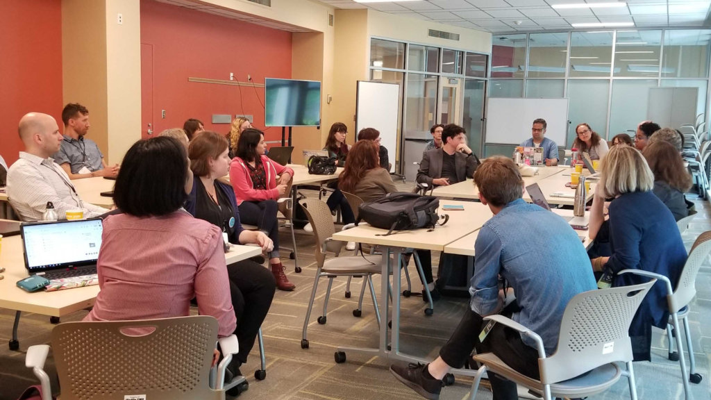Group of twenty-one symposium attendees sitting in a circle actively engaged in a workshop discussion session.