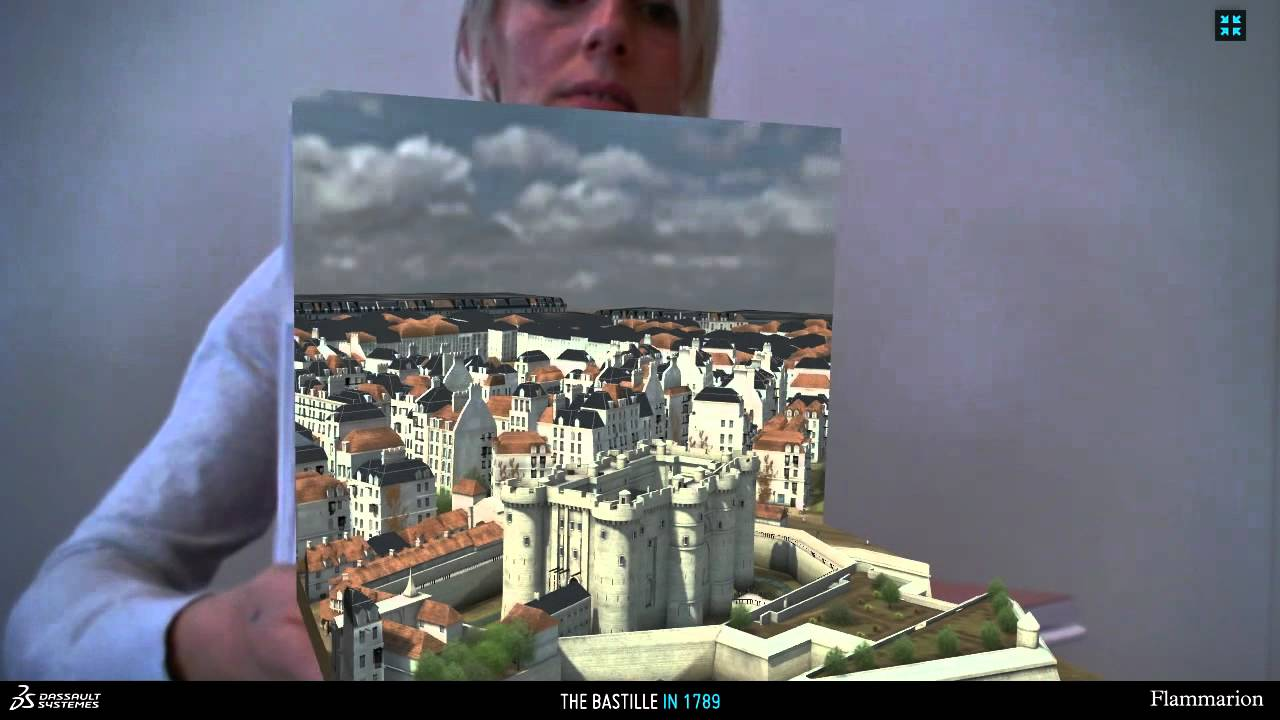 AR-enhanced book opened to show the 3D model of Paris emerging from the printed page