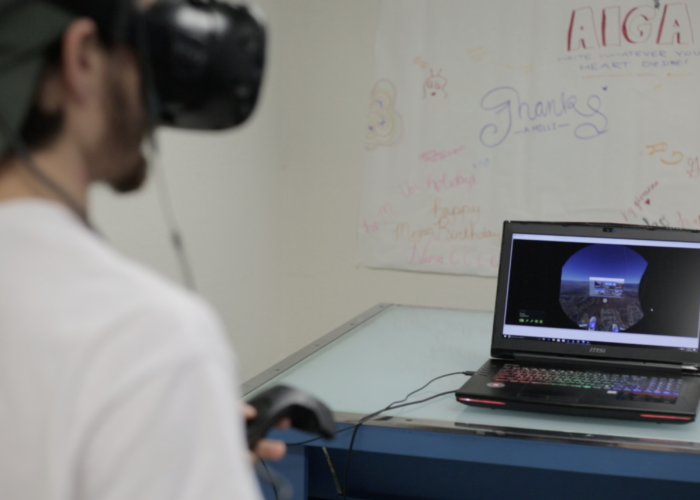 A college student, with their back toward the camera, is wearing a VR headset and holding controllers. In front of them is a gaming laptop with Google Earth displayed. There is a poster with hand drawn words in the background.
