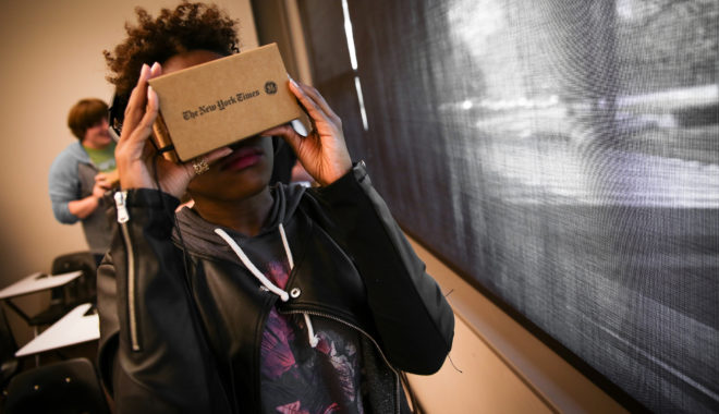 A college student stands by a classroom window wearing a leather jacket holding a Google Cardboard to their face.