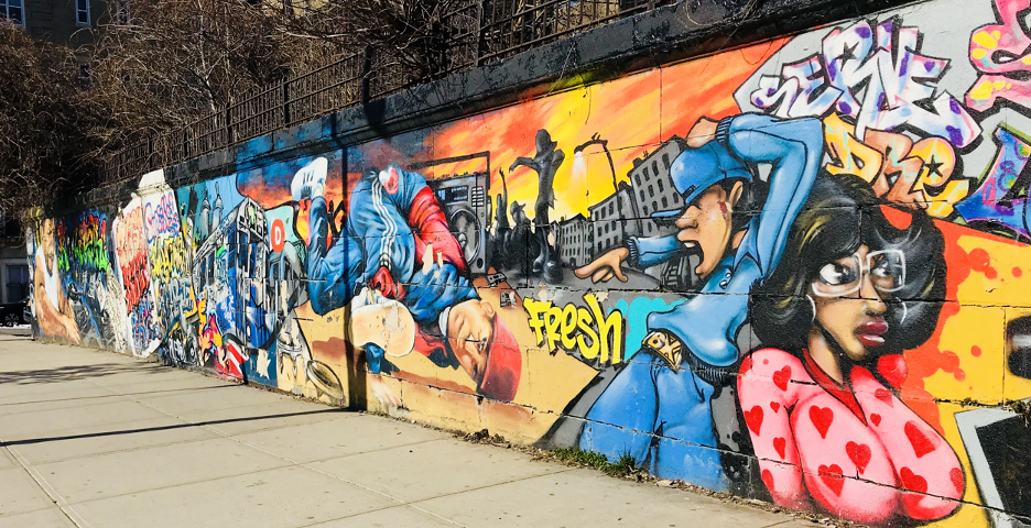 A brightly painted mural located on 166 th Street and Grand Concourse in the Bronx, depicting people in a Bronx cityscape.