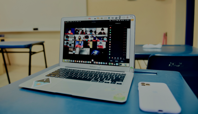 A laptop in a classroom displays a Zoom class in session.
