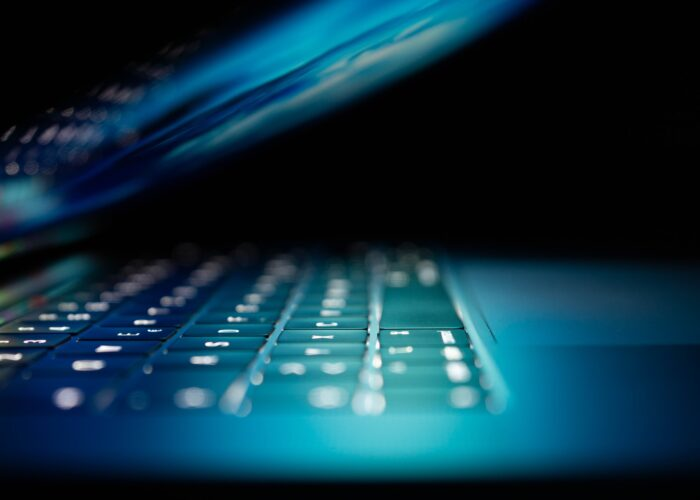 A dimly lit laptop light illuminates a keyboard as it closes.