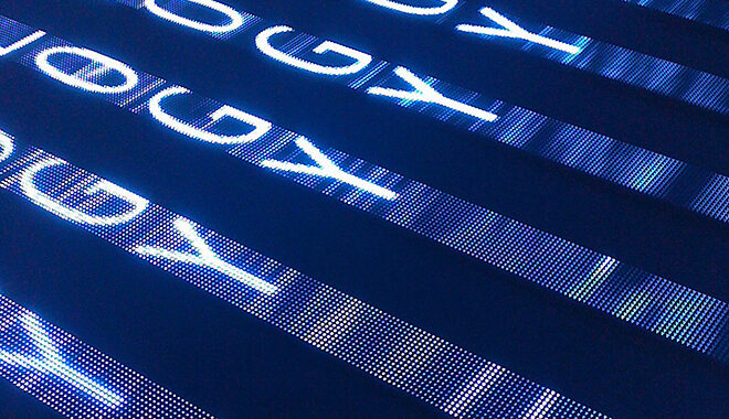 Letters O, G, and Y repeat in stylized rows, cutting diagonally across the frame in blue light. Photograph by Jeff Stvan from FOR[A] Photography and is provided under a Creative Commons NCBYND license.